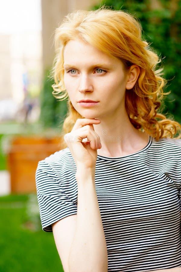 Stilvolles Porträt des jungen kaukasischen Mädchens mit dem gelockten blonden Haar stockfoto