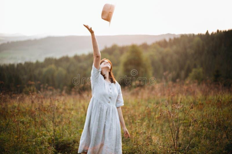 Stilvolles sorgloses boho Mädchen, das ihren Hut im Himmel im sonnigen Licht bei atmosphärischem Sonnenuntergang wirft Glückliche lizenzfreies stockbild