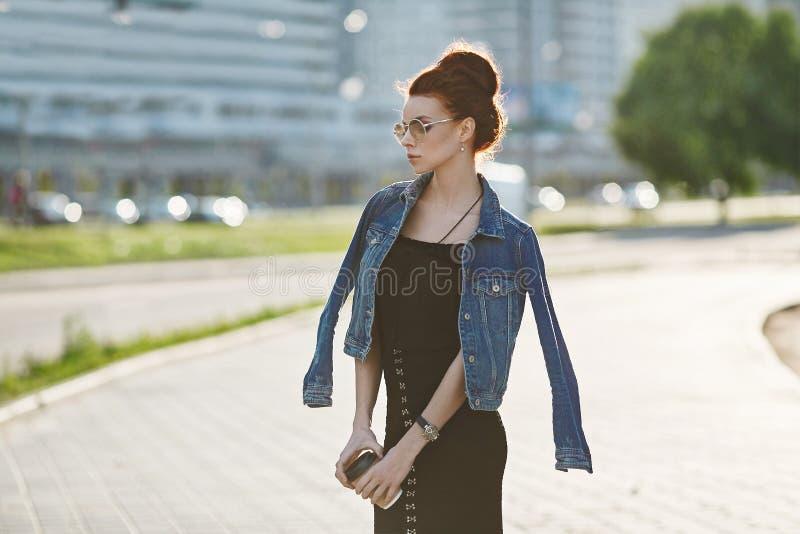 Stilvolles und schönes Brunettemodellmädchen in einer Jeansjacke, im modernen schwarzen Kleid und in modischen Gläsern, mit lizenzfreie stockbilder