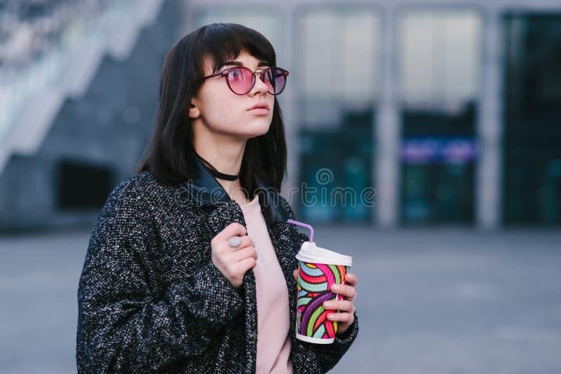 Stilvolles und schönes lächelndes Mädchen in den rosa Hippie-Gläsern, die einen Tasse Kaffee und einen Weg um die Stadt halten stockfotografie