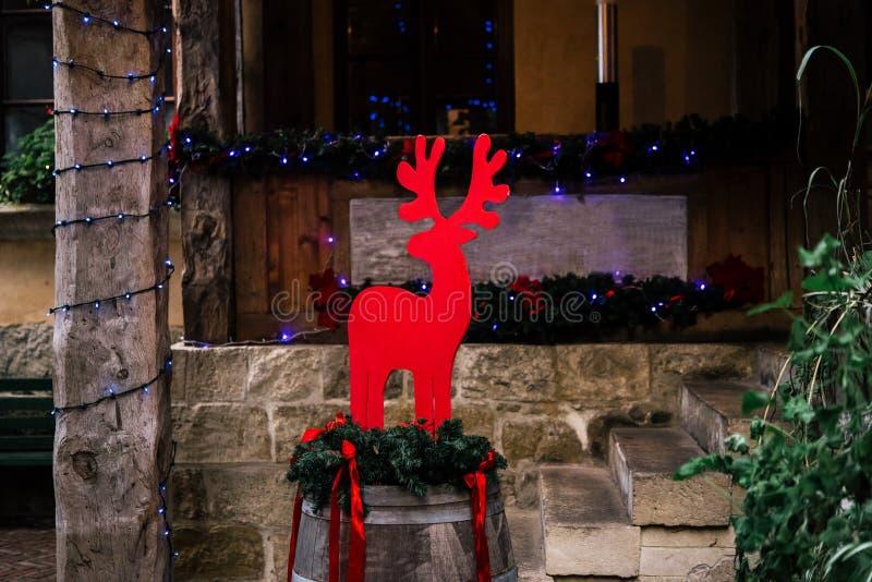 Stilvolles Weihnachtsrotwild auf Fass und Girlande beleuchtet, celebr stockfotografie