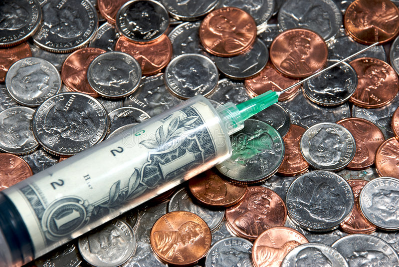 Stimulus #1. A close-up of a syringe filled with a dollar on a pile of coins royalty free stock image