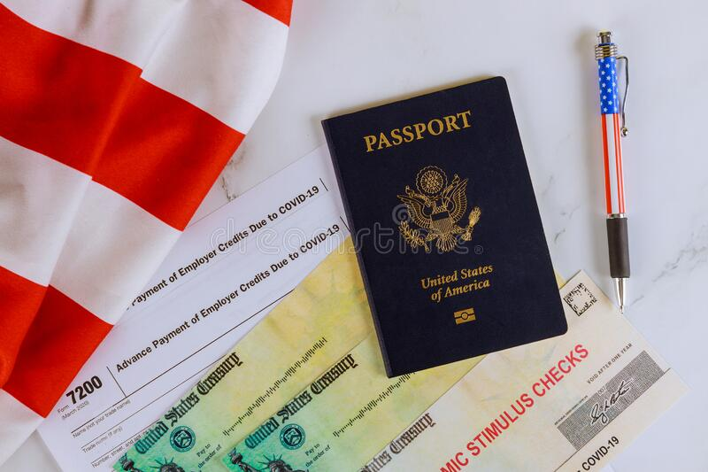 Stimulus relief check Passport of USA on American flag About Form 7200, Advance Payment of Employer Credits Due to COVID-19. Stimulus relief check on Passport of royalty free stock photo