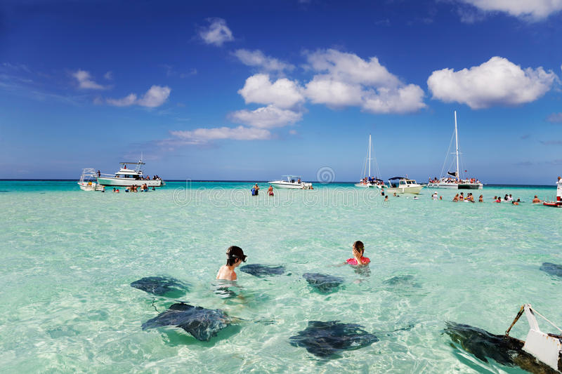 Stingrays City Grand Cayman. Brother & sister enjoy playing with the stingrays at the sandbar off Grand Cayman