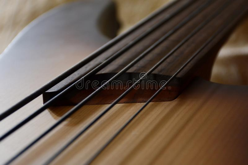 5 Srings Fretless Bass Guitar with Black Strings. 5 Stings Bass Guitar wood Color With Black Strings and Black Accesories stock photo
