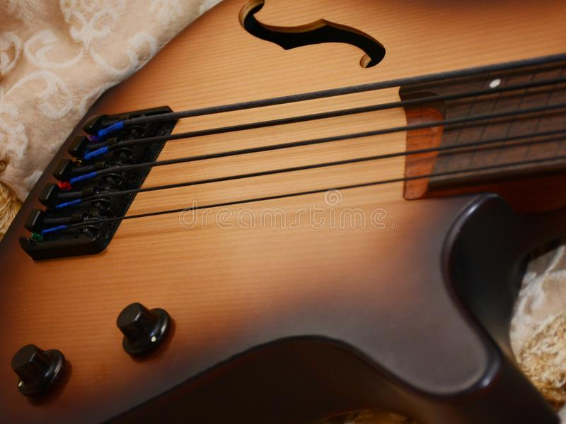 5 Srings Fretless Bass Guitar with Black Strings. 5 Stings Bass Guitar wood Color With Black Strings and Black Accesories royalty free stock photography