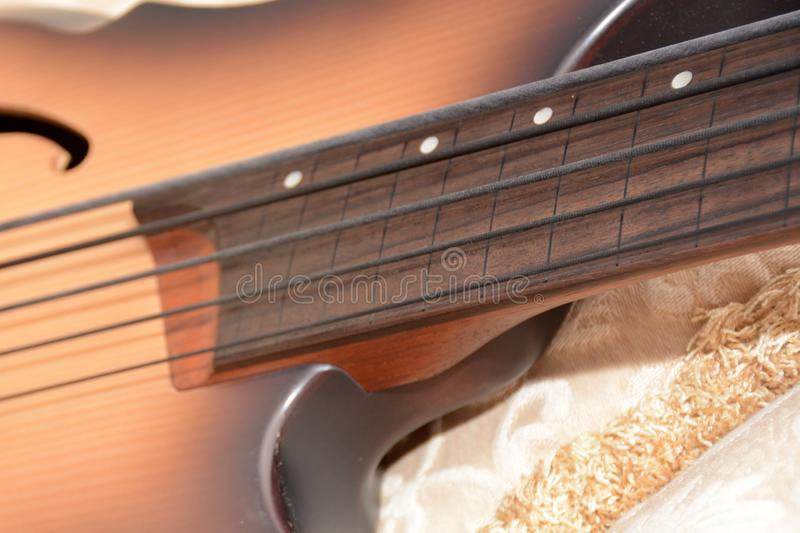 5 Srings Fretless Bass Guitar with Black Strings. 5 Stings Bass Guitar wood Color With Black Strings and Black Accesories royalty free stock photos