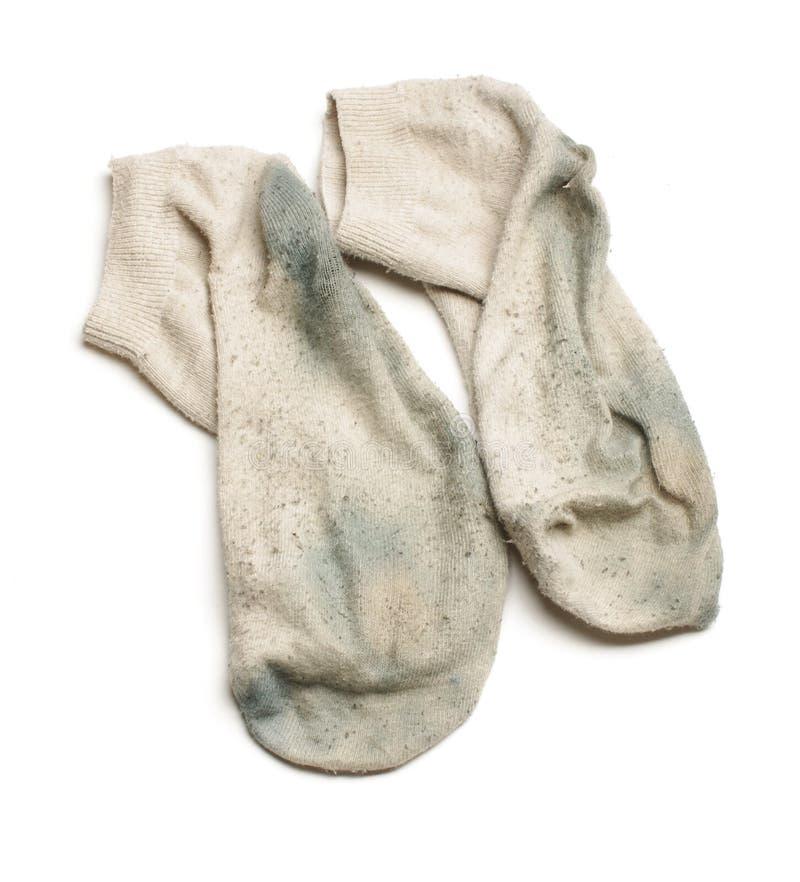 Stinkande smutsiga sockor som isoleras på den vita bakgrunden arkivfoton