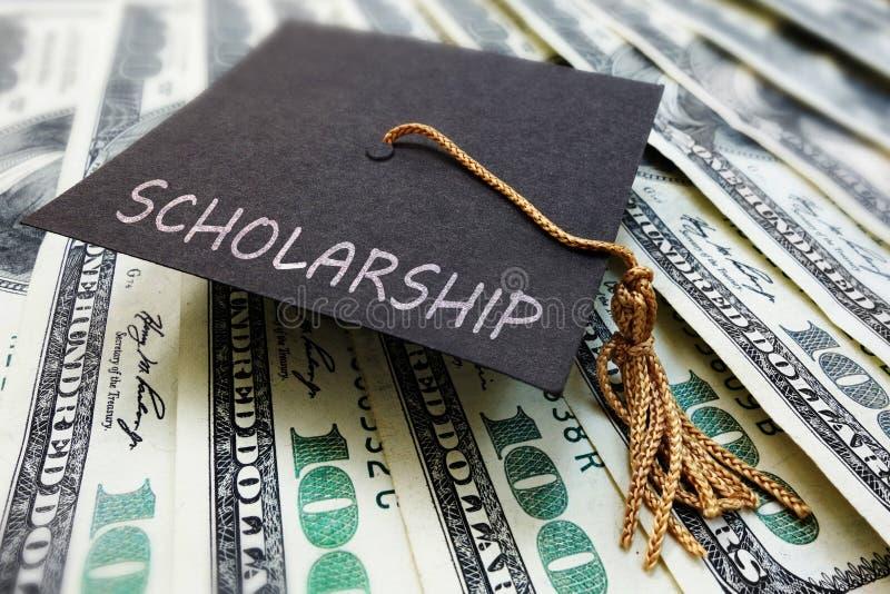 Stipendiumkappe auf Geld stockbild