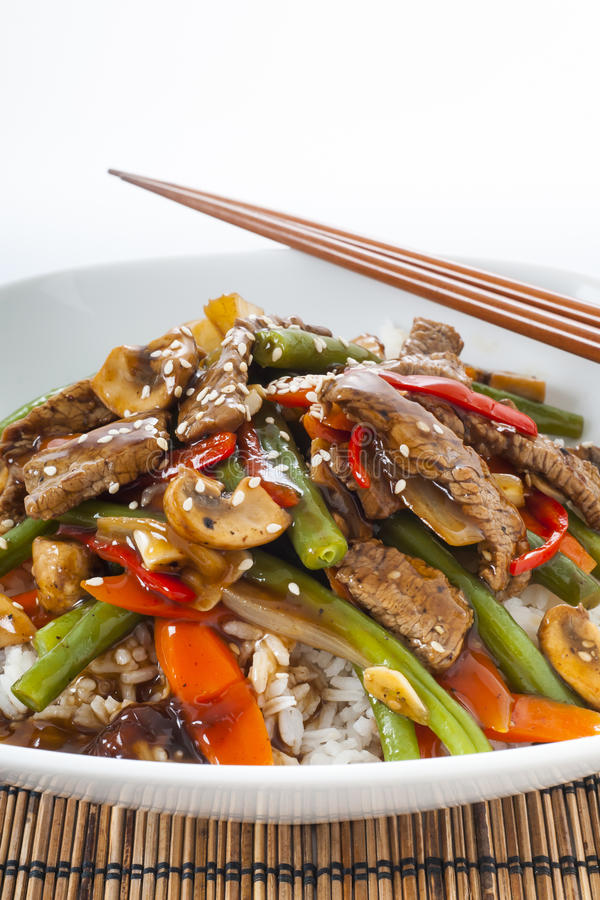 Stir fried Beef. Asian style stir fried bee with green beans, mushrooms, red peppers and carrots accompanied by white rice and chopsticks royalty free stock images