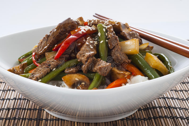 Stir fried Beef. Asian style stir fried bee with green beans, mushrooms, red peppers and carrots accompanied by white rice and chopsticks royalty free stock photography