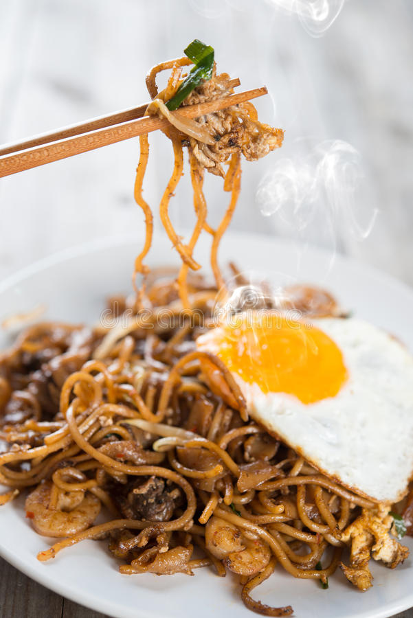 Stir fried Char Kuey Teow. Stir fried char kway teow with prawns and chopstick over wooden background stock photo