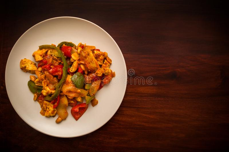 Stir fried chicken with peanuts. On wooden background stock images