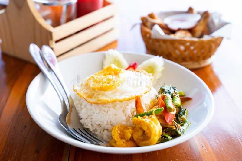 Stir fried curry with shrimp and fried egg. Thai food royalty free stock image