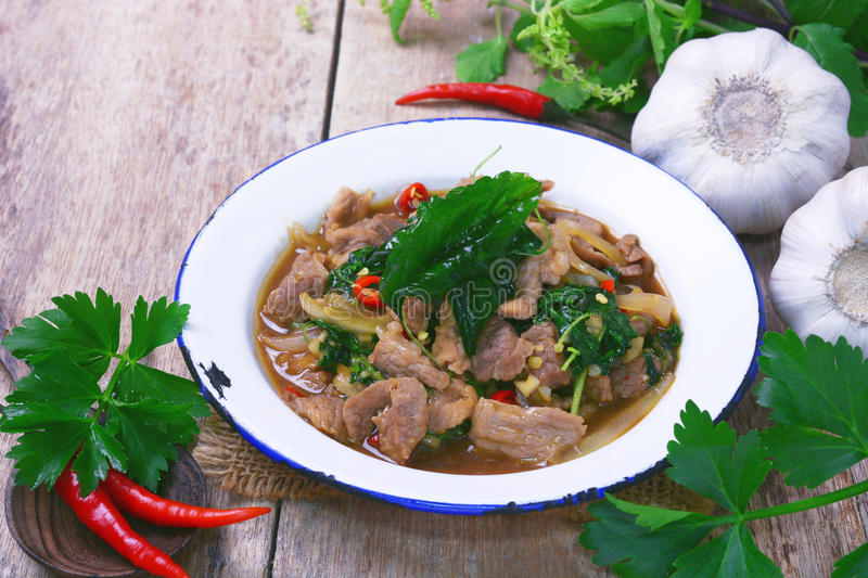 Stir fried hot and spicy sauce with pork, crispy basil leaf on top. stock photography