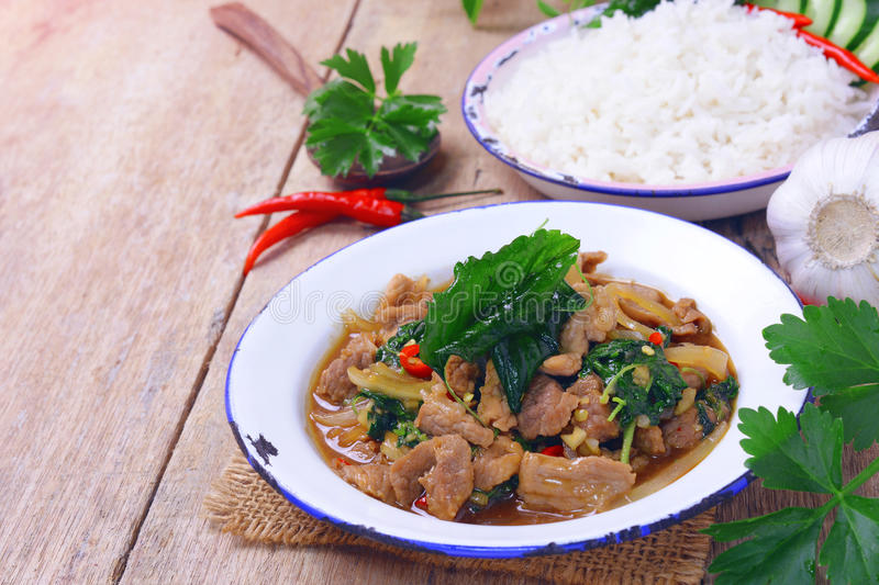 Stir fried hot and spicy sauce with pork, crispy basil leaf on top. stock images