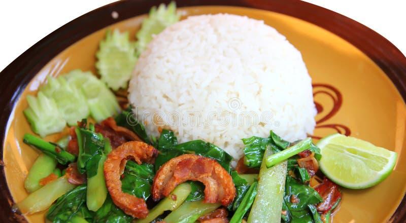 Stir-fried kale with crispy pork and rice stock image