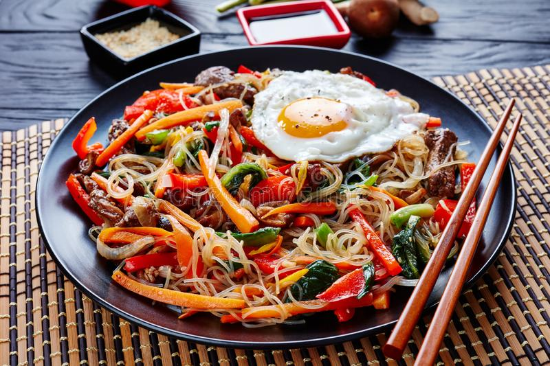 Stir fried noodles with vegetables, beef, close up. Korean japchae or chapchae stir fried noodles with vegetables: red bell pepper, carrot, shiitake mushrooms royalty free stock photos