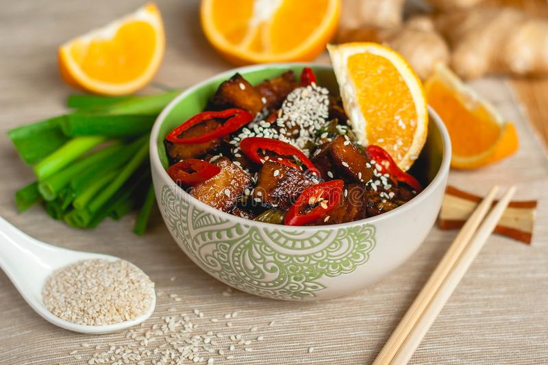 Stir-fried orange ginger tofu with sesame onion and chili spices in a bowl with chopsticks on a table royalty free stock photos