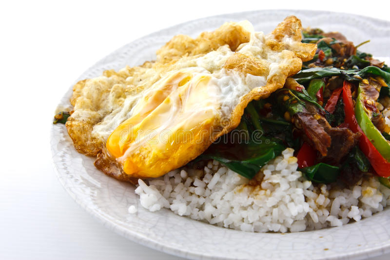 Stir fried pork with basil and egg served with rice. On isolated stock image