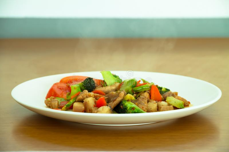 Stir fried pork with carrots, tomatoes and broccoli in a plate o stock image