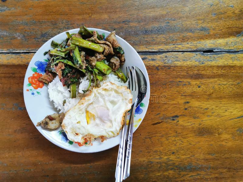 Stir fried pork curry and vegetable with fied egg, spicy Thai food. Street food royalty free stock images