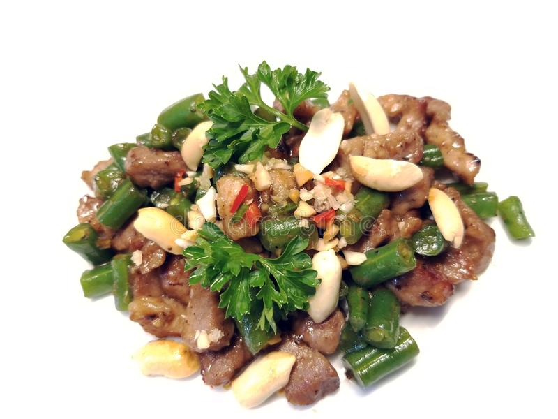 Stir Fried Pork 1. Stir fried pork with peanuts, string beans, and parsley on a white background stock images