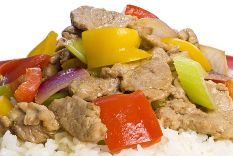 Stir Fried Pork and Vegetables. Stir fried pork tenderloin with colorful vegetables on a bed of rice royalty free stock images