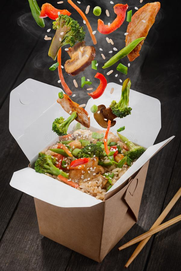 Stir-fried rice in box. Falling down ingredients such as chicken meat, broccoli, pepper, lettuce, asparagus, rice and sesame seeds. Asian food delivery royalty free stock photo
