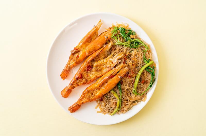 Stir-fried rice vermicelli and water mimosa with river prawns. On plate stock image