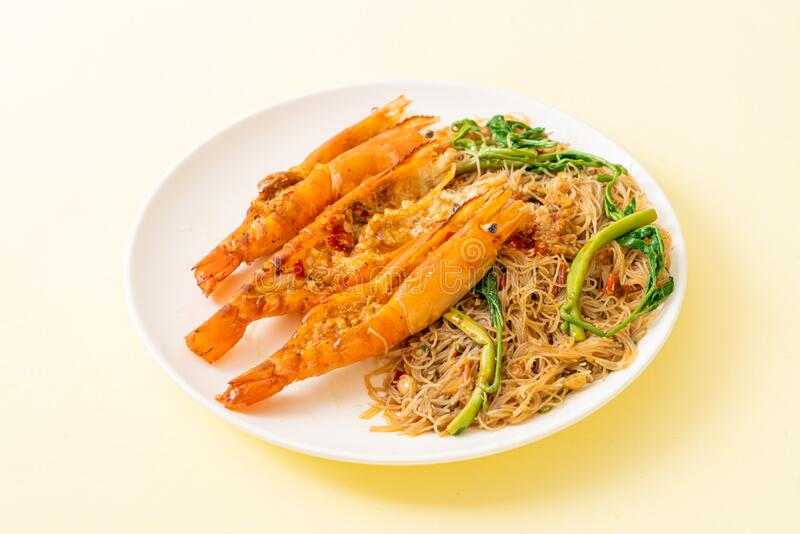 Stir-fried rice vermicelli and water mimosa with river prawns. On plate royalty free stock image