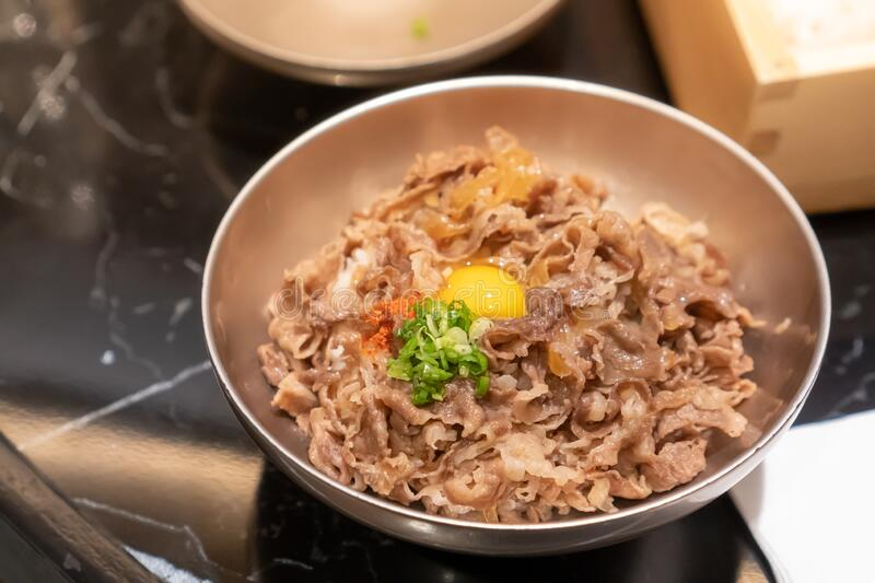 Stir-fried sliced pork with sweet sauce topped on Japanese rice topping with a quill egg. Put in a small stainless steel bowl stock images