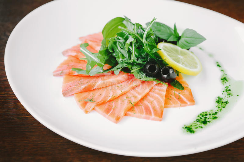 Stir fried sliced salmon with olive, lemon and herbs on white pl stock photos