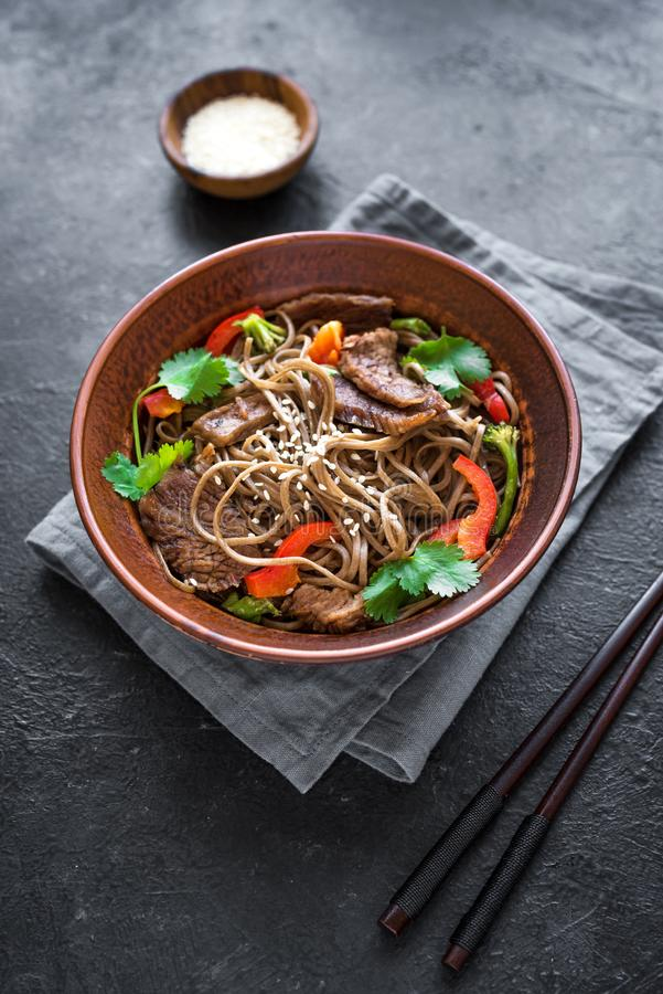 Stir fried soba and beef. Stir fry with soba noodles, beef and vegetables. Asian healthy food, stir fried meal in bowl on black background royalty free stock image
