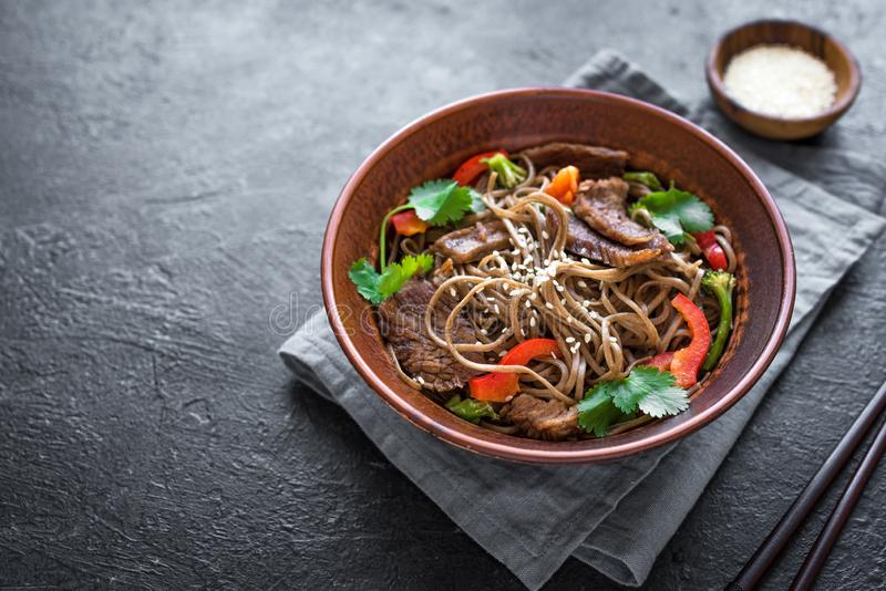 Stir fried soba and beef. Stir fry with soba noodles, beef and vegetables. Asian healthy food, stir fried meal in bowl on black background, copy space stock photo