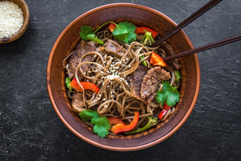 Stir fried soba and beef. Stir fry with soba noodles, beef and vegetables. Asian healthy food, stir fried meal in bowl on black background, copy space royalty free stock image