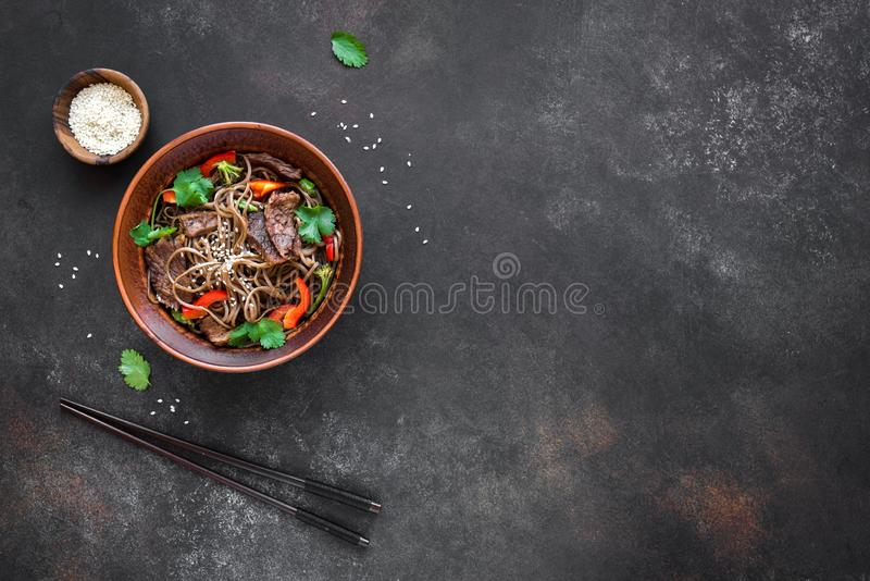 Stir fried soba and beef. Stir fry with soba noodles, beef and vegetables. Asian healthy food, stir fried meal in bowl on black background, copy space stock image
