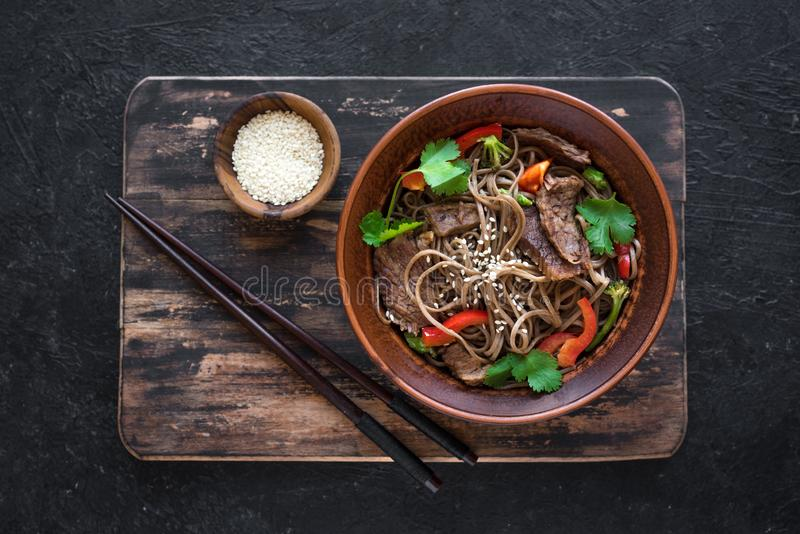 Stir fried soba and beef. Stir fry with soba noodles, beef and vegetables. Asian healthy food, stir fried meal in bowl on black background, top view stock photos