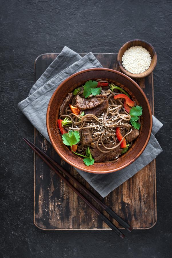 Stir fried soba and beef. Stir fry with soba noodles, beef and vegetables. Asian healthy food, stir fried meal in bowl on black background, top view, copy space royalty free stock photography