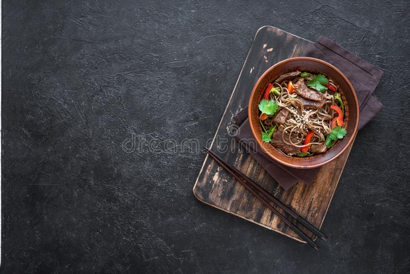 Stir fried soba and beef. Stir fry with soba noodles, beef and vegetables. Asian healthy food, stir fried meal in bowl on black background, top view, copy space royalty free stock image