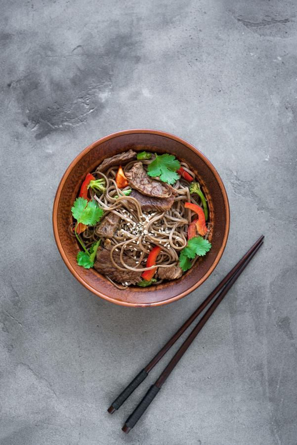 Stir fried soba and beef. Stir fry with soba noodles, beef and vegetables. Asian healthy food, stir fried meal in bowl on dark background, top view, copy space royalty free stock images
