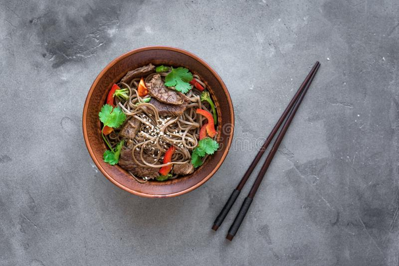 Stir fried soba and beef. Stir fry with soba noodles, beef and vegetables. Asian healthy food, stir fried meal in bowl on dark background, top view, copy space stock photo