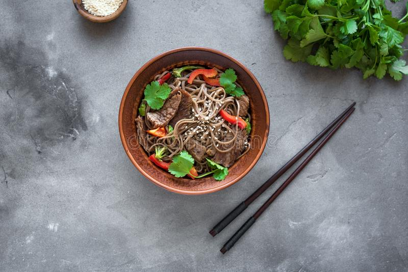 Stir fried soba and beef. Stir fry with soba noodles, beef and vegetables. Asian healthy food, stir fried meal in bowl on dark background, top view, copy space stock image