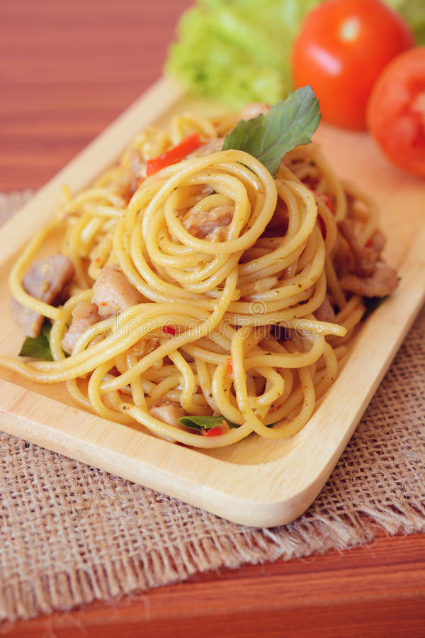 Stir-fried spicy spaghetti with chicken. Thai style. Basil, chicken, closeup, dish, thailand, italian, meal, pepper, spice, oriental, plate, wooden plate stock photography