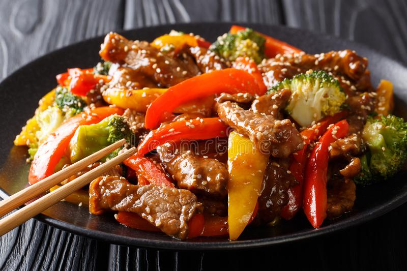 Stir-fried teriyaki beef with red and yellow bell pepper, broccoli and sesame seeds close-up on the table. horizontal. Stir-fried teriyaki beef with red and royalty free stock images