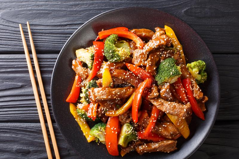 Stir-fried teriyaki beef with red and yellow bell pepper, broccoli and sesame seeds close-up on the table. horizontal top view. Stir-fried teriyaki beef with red royalty free stock image
