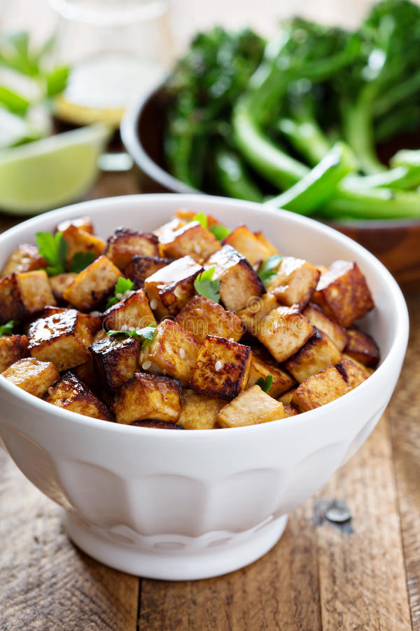Stir fried tofu in a bowl. With sesame and greens stock images