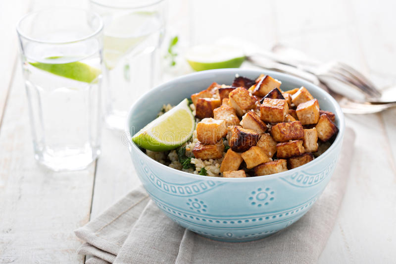 Stir fried tofu in a bowl. With sesame and greens stock photos