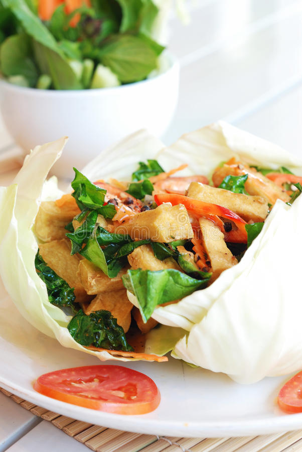 Stir fried tofu. Vegetarian food - stir fried tofu and mixed vegetables serves in cabbage container royalty free stock photo