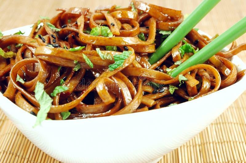 Stir Fried Udon. Bowl of stir fried udon noodles garnished with black sesame seeds and fresh mint with green chopsticks royalty free stock photo